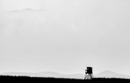 Obraz Minimalistický černobílý foto obraz s posedem a horami na pozadí