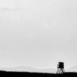 Minimalistický černobílý foto obraz s posedem a horami na pozadí